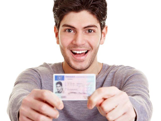 Hombre sonriendo y sosteniendo el carnet de conducir