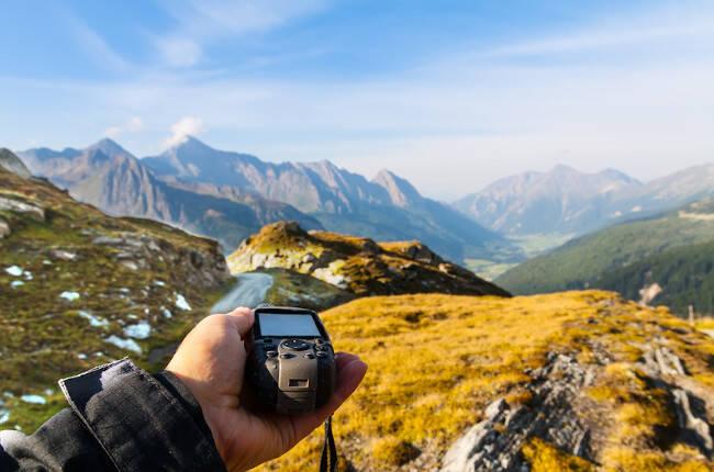 Artículo gps para quad y moto: imagen de un paisaje junto con una mano sujetando un gps.