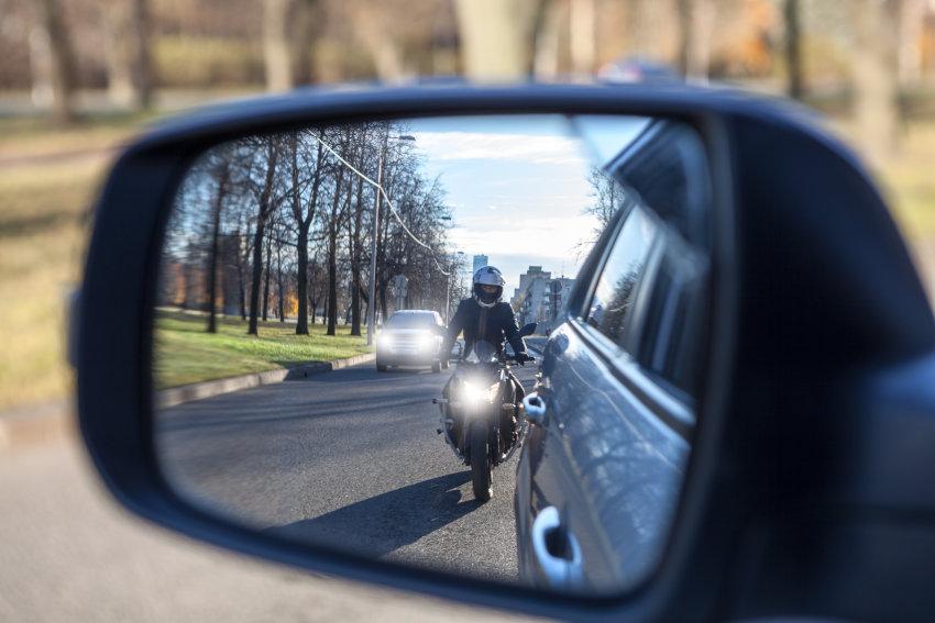 imagen desde el retrovisor derecho de un coche de una moto adelantando por la derecha