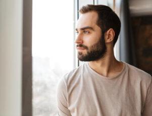 hombre joven mirando por la ventana