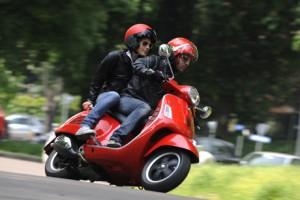 chico con pasajera tomando una curva con una scooter Vespa de color rojo