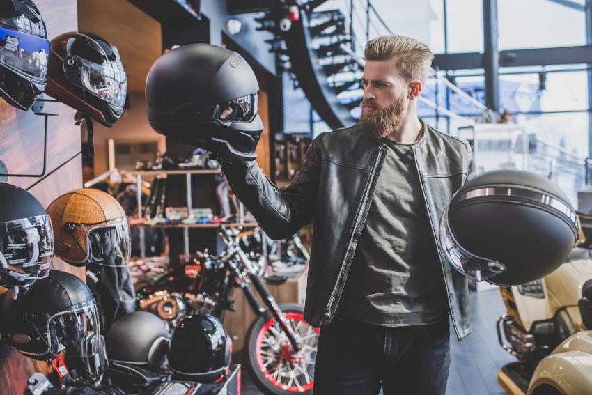 tienda de accesorios de moto en la que se encuentra un hombre joven escogiendo entre dos cascos de moto