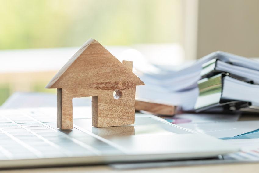 figura de una casita de madera encima del teclado de un ordenador y de un montón de papeles