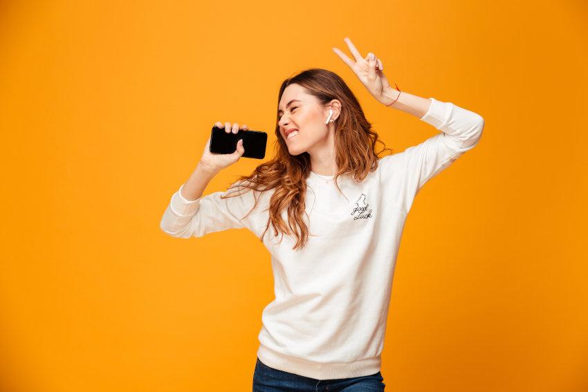 chica escuchando música desde el móvil con cascos inalámbricos y bailando
