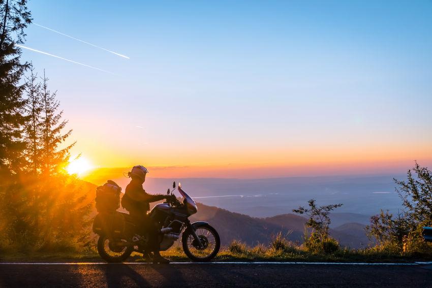 motoristas parado en el arcén de una carretera contemplando el atardecer de un paisaje de montaña