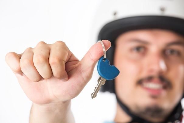 Motero con una llave en su mano.