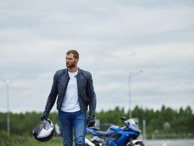 Motorista alejándose de su moto aparcada