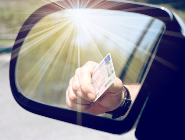 conductor visto desde el retrovisor, sacando por la ventanilla del coche la mano con el carnet de conducir