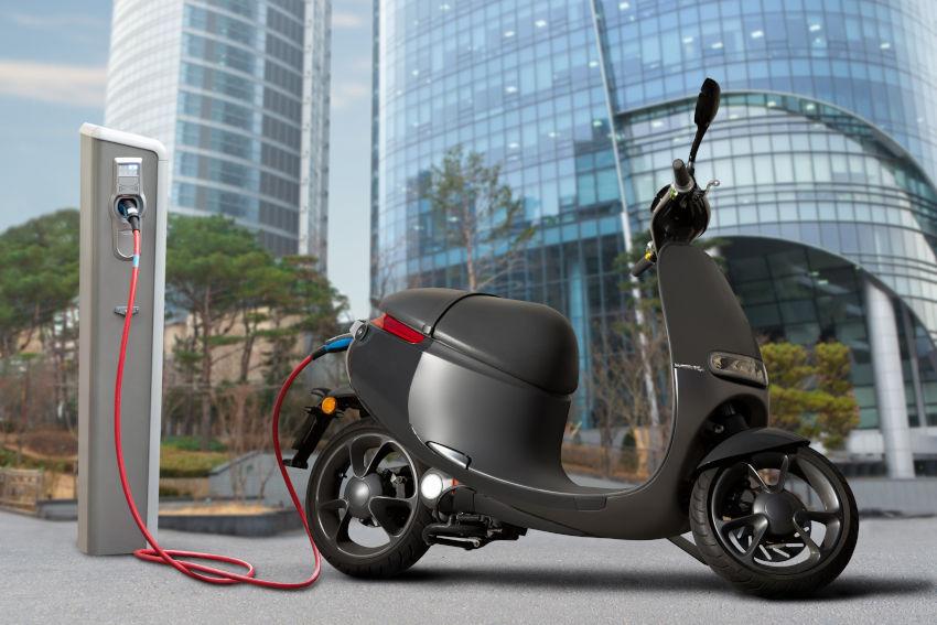 moto eléctrica tipo scooter conectada a un punto de carga de una ciudad