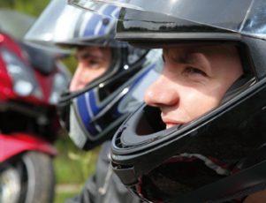hombre sonriendo con un casco de moto de color negro