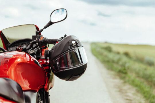 moto deportiva parada en un camino con un casco integral colgado del manillar