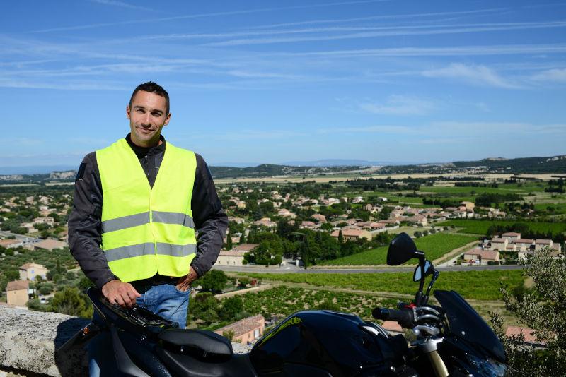 Motorista con chaleco reflectante apoyado en su moto