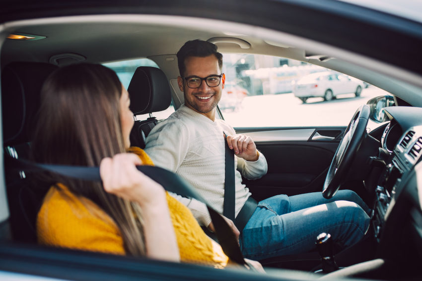 pareja poniéndose el cinturón de seguridad del coche