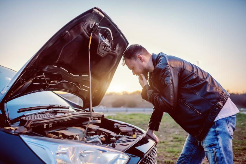 hombre mirando el motor de un coche con el capó abierto