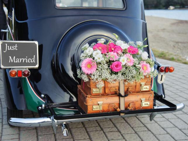 """decoración floral de boda en la parte trasera de un coche clásico con cartel """"just married"""""""