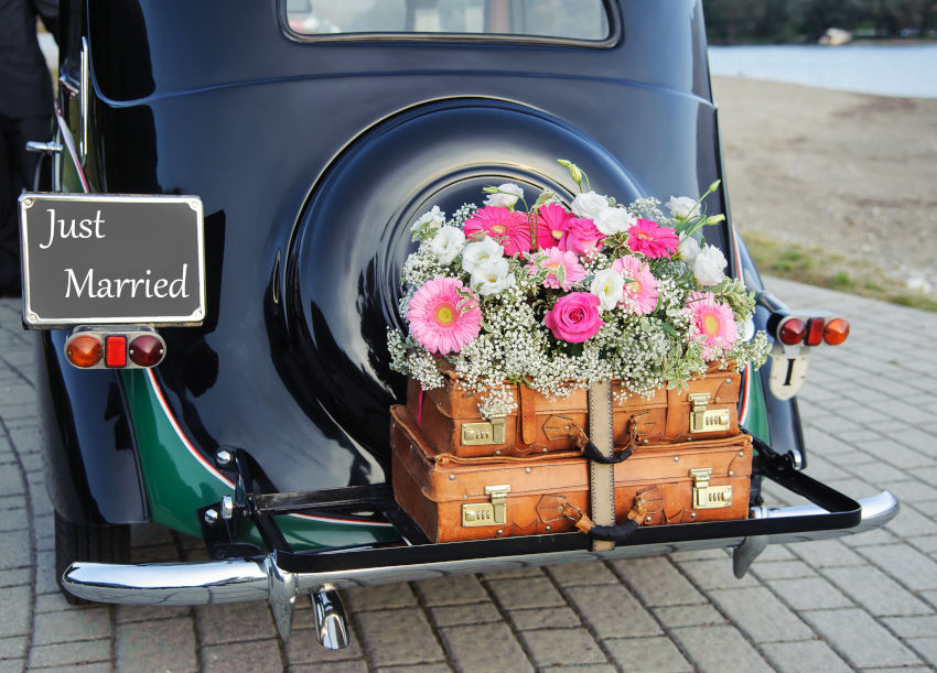 "decoración floral de boda en la parte trasera de un coche clásico con cartel ""just married"""