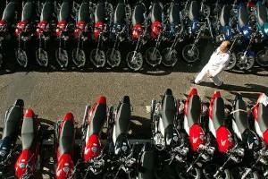 hombre paseando entre filas de motos nuevas aparcadas fuera