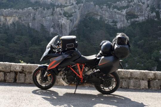 Moto estacionada en un mirador frente a un paisaje. La moto mucho equipaje