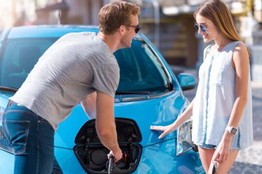 Chico y chica enchufando a la red de carga su coche eléctrico