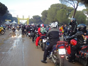 Un grupo de motoristas hace fila en una calle un día de lluvia.