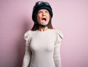 plano medio de una mujer con casco de moto, mirando hacia arriba y gritando