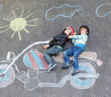 Moto pintada con tiza en el suelo y niños