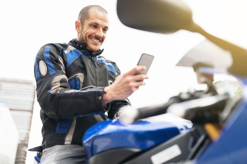 hombre con equipamiento motero subido en su moto aparcada, manejando su teléfono móvil