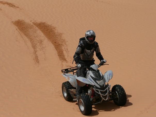 hombre conduciendo un quad en el desierto