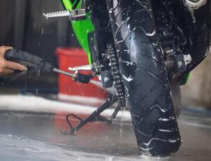 limpieza de una moto con manguera en un garaje