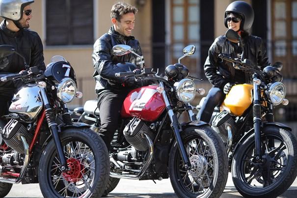 El diccionario motero: tres jóvenes conversan en la calle, montados a sus motos.