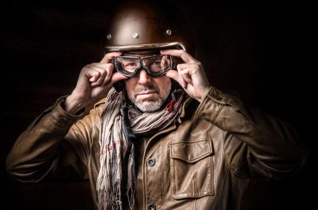 hombre con ropa y casco de moto tipo vintage poniéndose gafas para conducir