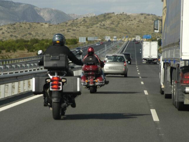 2 motoristas adelantando por la izquierda a un camión en una autopista
