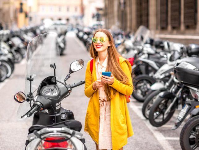 chica vestida de amarillo al lado de un scooter con el móvil en la mano