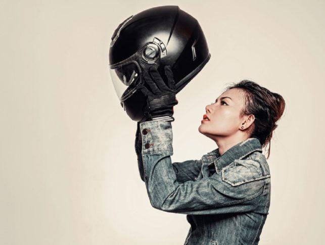 chica probándose un casco integral de moto