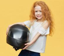 niña pelirroja sosteniendo un casco de moto integral