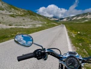 primer plano del manillar de una moto donde se ve el espejo retrovisor y el cuentakilómetros y de fondo un paisaje