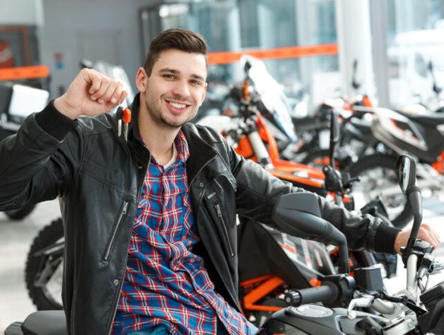 hombre joven sentado en una moto nueva y mostrando las llaves en un concesionario