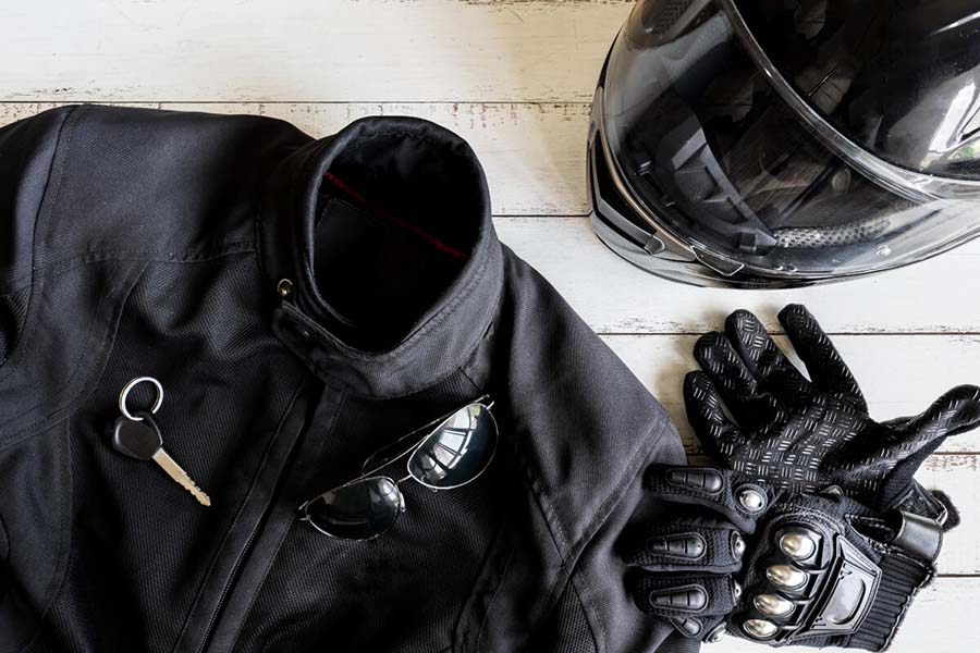 Chaqueta negra, llaves, gafas, casco y guantes para motero