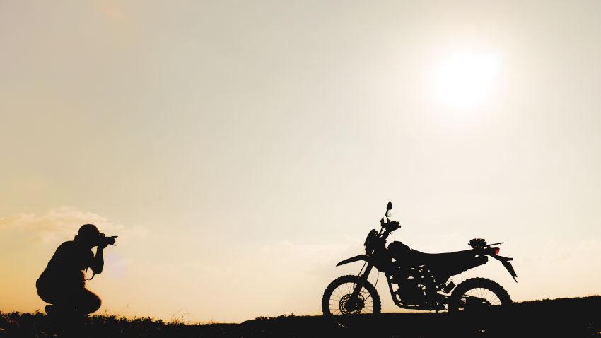 hombre en cuclillas haciendo una foto de una moto al atardecer