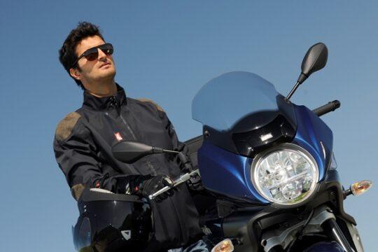 Un joven luce sus gafas de sol para conducir sobre su moto. | Piaggio Group
