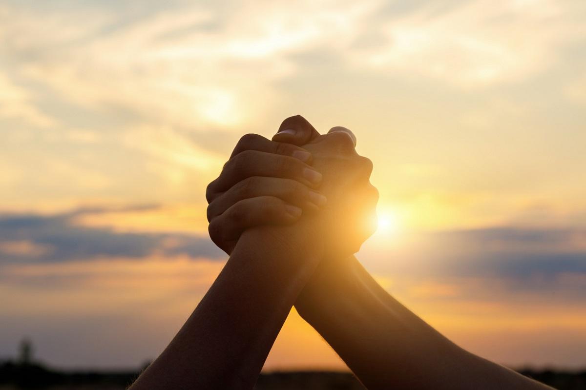 manos entrelazadas en puesta de sol