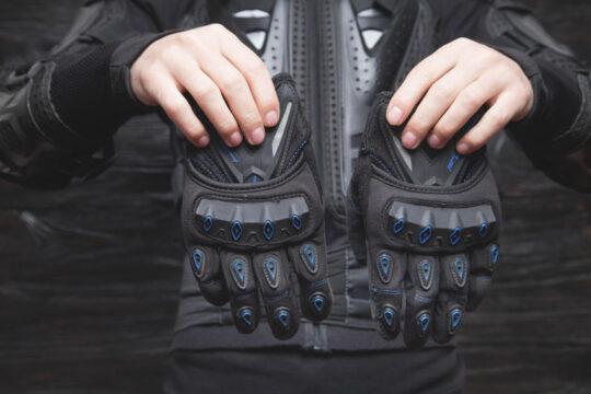 motorista sujetando con sus manos un par de guantes de moto