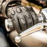mano de un motorista sujeta al manillar y protegida por un guante