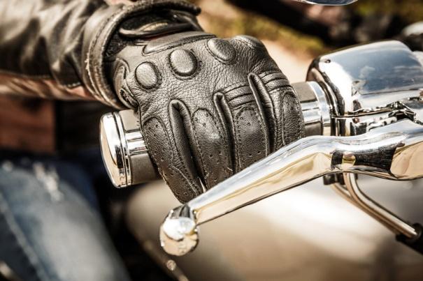 Guantes de moto: imagen de la mano de un motorista sujeta al manillar y protegida por un guante.