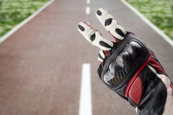 Saludo motero en V con guantes de moto de verano