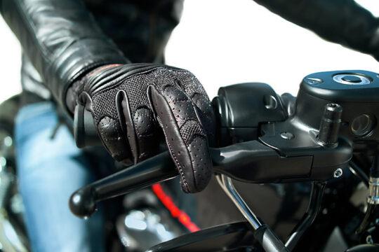 Mano con guante negro de moto accionando la maneta de freno de una motocicleta