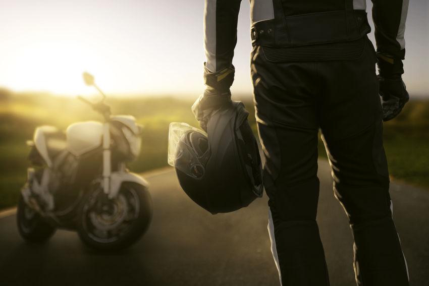 motorista de espaldas con casco de moto en su mano mirando hacia su moto