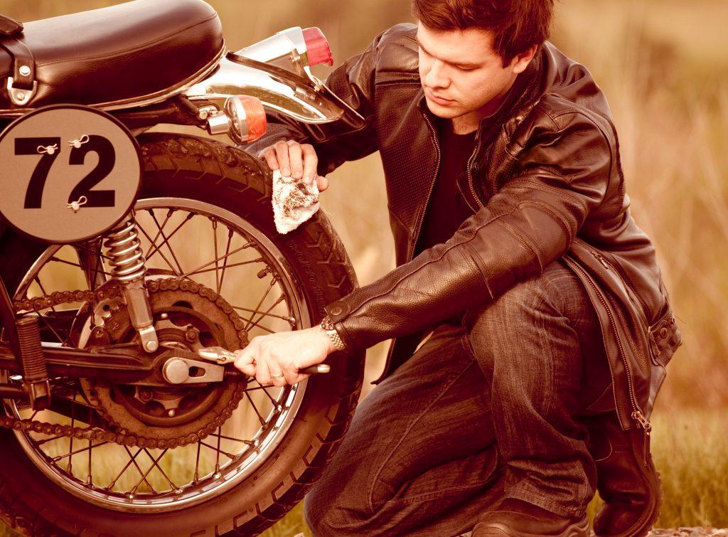 hombre apretando la rueda de una moto con una llave inglesa