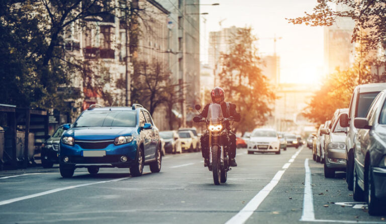 motorista circulando en paraleo a un coche por las calles de una ciudad