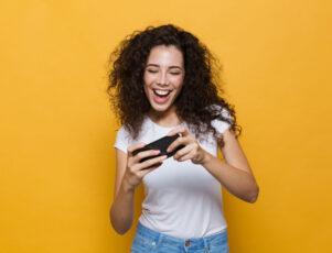 mujer joven sonriendo mientras juega con su móvil